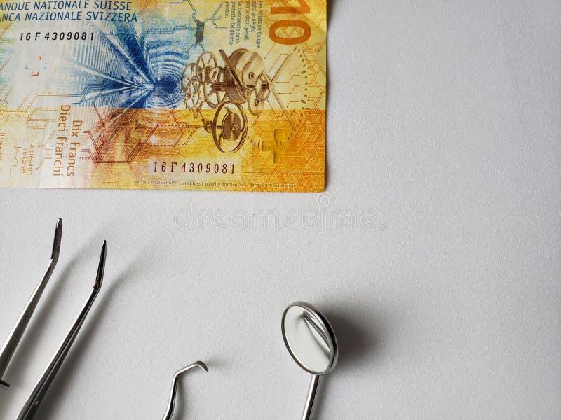 口头回顾和十法郎瑞士钞票的牙医器物  免版税库存照片