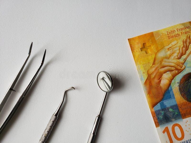 口头回顾和十法郎瑞士钞票的牙医器物  库存图片