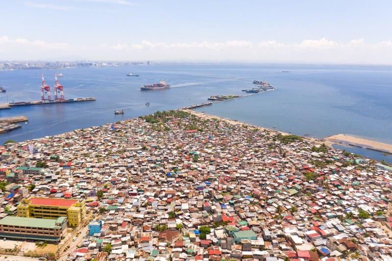 口岸在马尼拉,菲律宾 有货物起重机的海港 与恶劣的区域的都市风景和在距离的商业中心 图库摄影