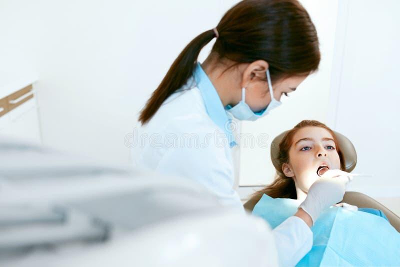口腔医学 牙医与在牙齿诊所的女孩牙一起使用 图库摄影