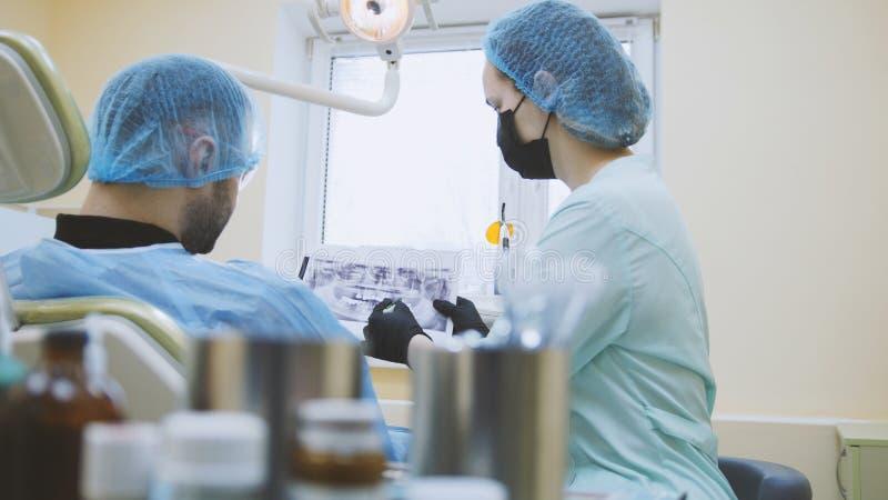 口腔医学-考试医生和患者在牙齿办公室,嘴 免版税图库摄影