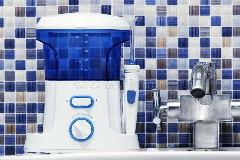 口腔卫生,卫生间反对概念 装腔作势地说清洗在水槽的牙irrigator现代工具 库存照片
