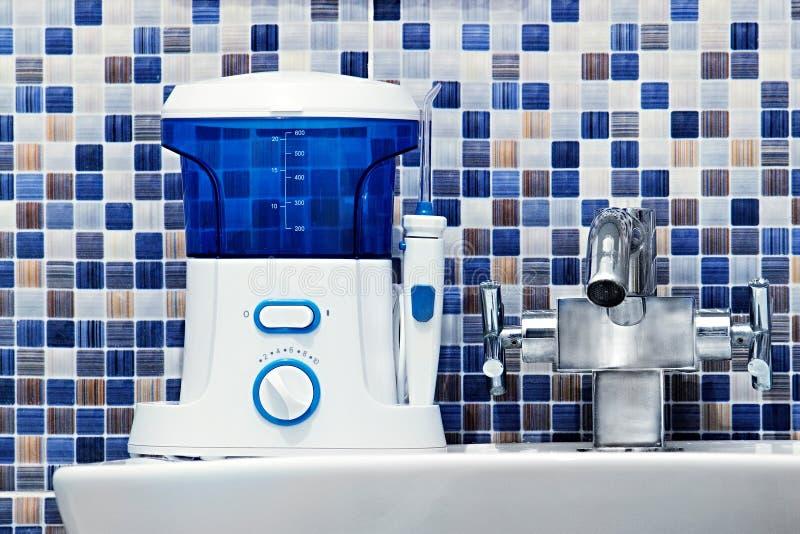 口腔卫生,卫生间反对概念 装腔作势地说清洗在水槽的牙irrigator现代工具 免版税库存图片
