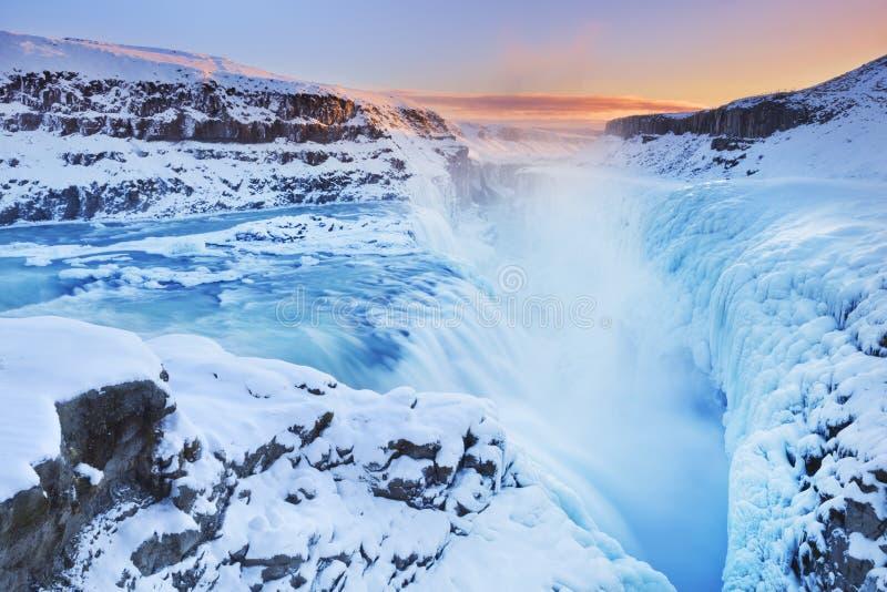 冻古佛斯瀑布在冰岛下跌在冬天在日落 免版税库存照片