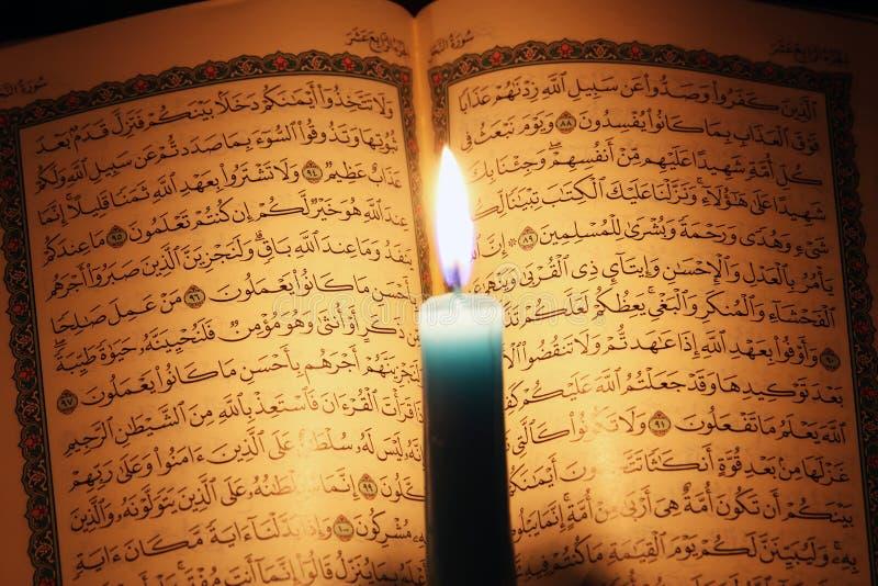 古兰经或古兰经圣经与蜡烛在烛光 免版税图库摄影