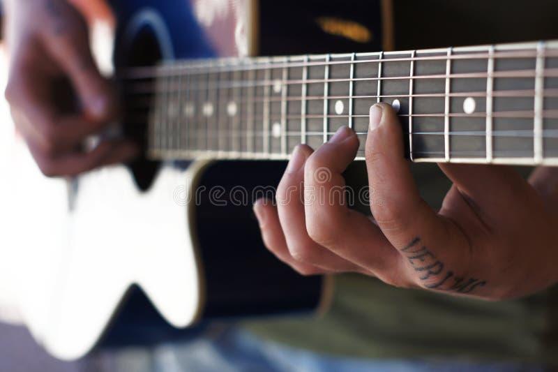 古典吉他演奏员的手有手指在串和吉他的脖子的 库存图片