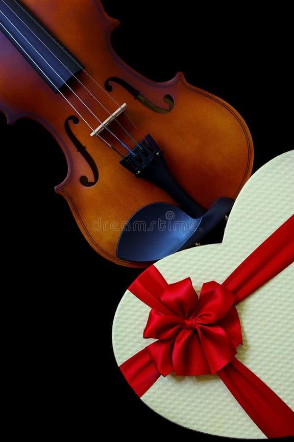 古典小提琴和带红丝带弓的心形礼盒的特写 免版税库存照片