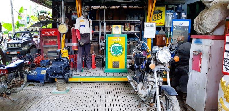 古典摩托车停放着油箱、钟、冰箱和服装,在复古加油站展示木偶 库存图片