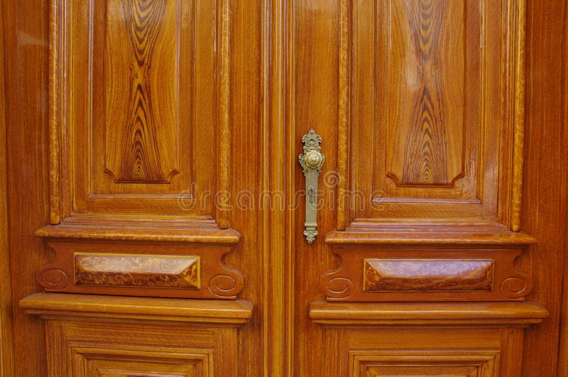 古典木与金黄古色古香的门把手和匙孔的入口双门 图库摄影