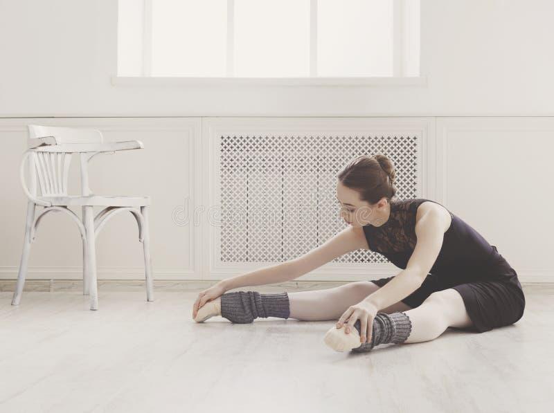 古典跳芭蕾舞者做舒展在类 库存照片