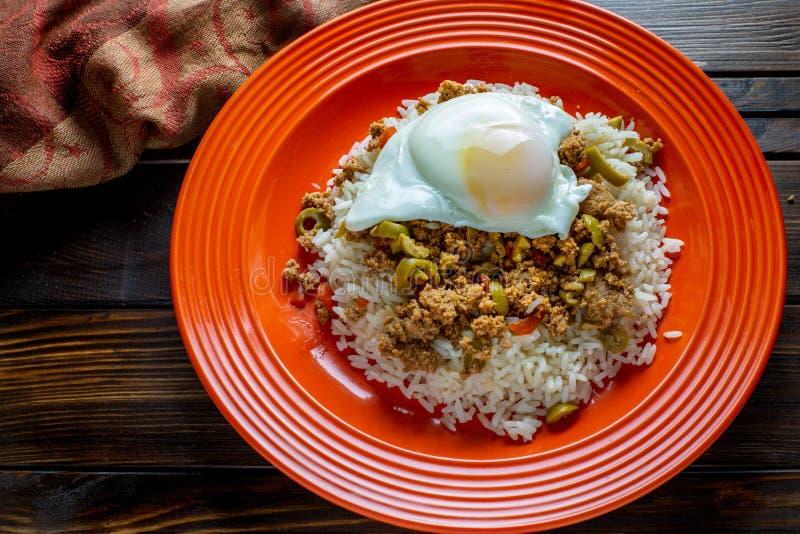古巴盘由绞细牛肉制成在米床上服务与晴朗的边的在一块红色板材的鸡蛋在一个木厨房选项的Picadillo 库存照片