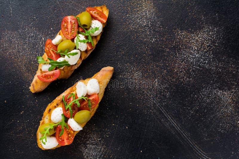 古暗背景下的樱桃番茄、莫扎里拉、橄榄和罗勒烤面包 库存照片