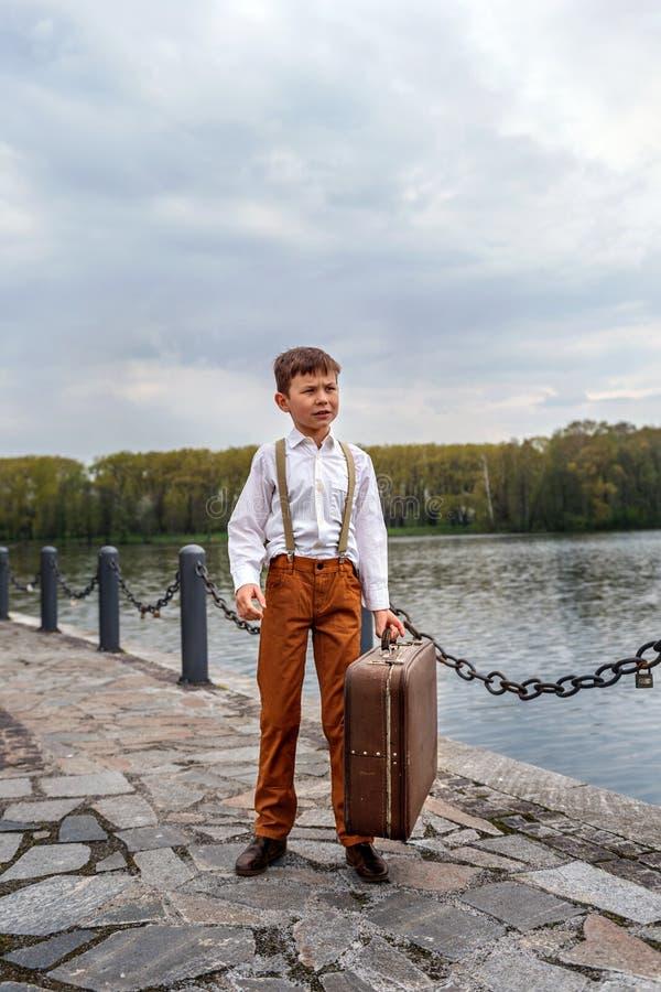 古板的土气衣裳的小男孩的笨蛋带着站立在码头的到来驻地的葡萄酒手提箱  库存图片