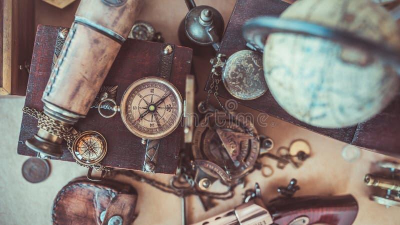 古板的指南针,在旧世界地图的望远镜 库存图片