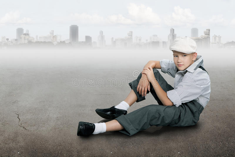 古板的男孩坐地面近的城市 免版税库存图片