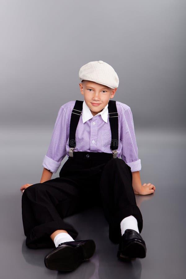 古板的男孩坐灰色背景 免版税库存图片