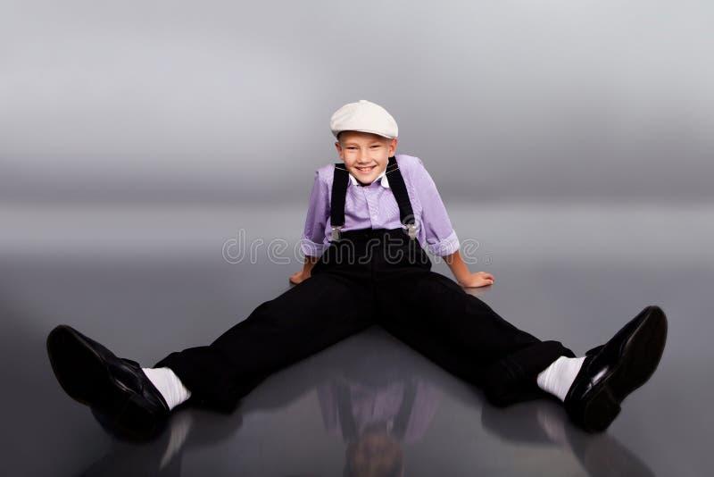古板的男孩坐灰色背景 图库摄影
