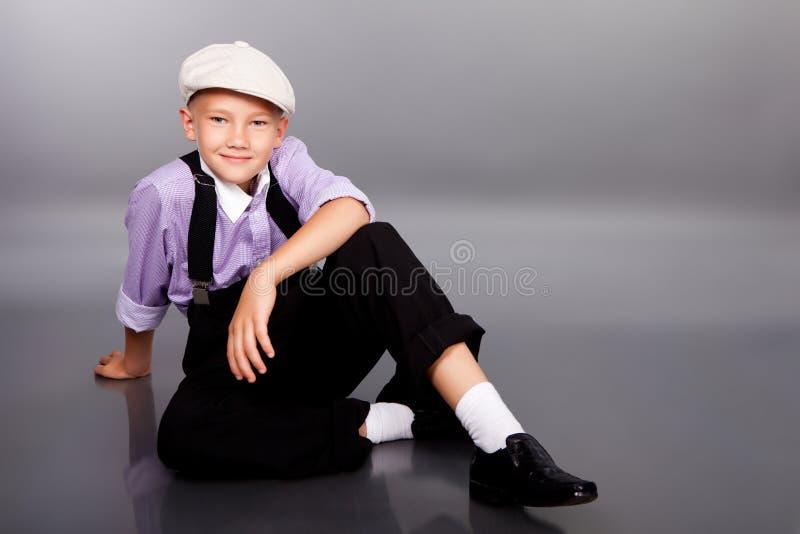 古板的男孩坐灰色背景 免版税库存照片