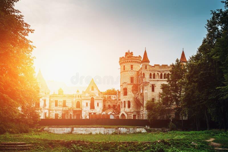 古老中世纪城堡或堡垒与塔楼和塔在绿色森林中日落的点燃 免版税库存照片