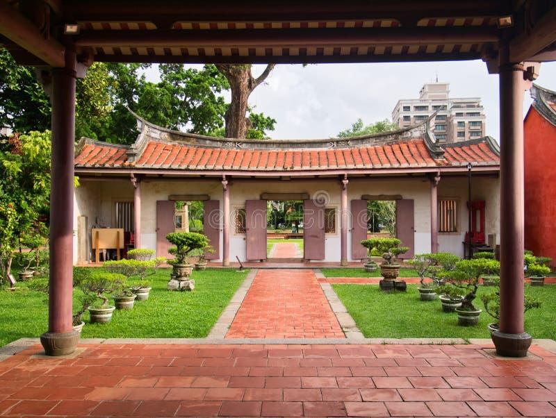 古老中国式红色上色了门和门道入口和盆景 库存图片