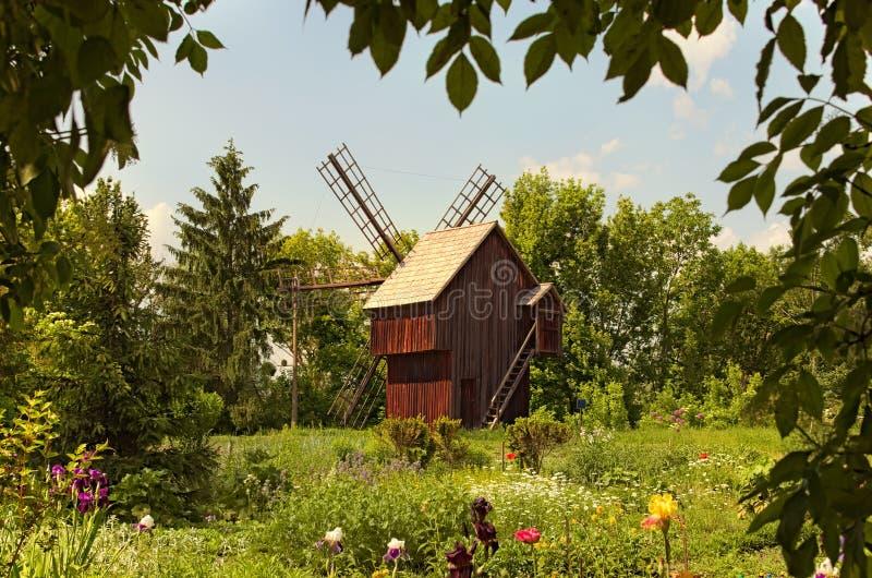 古老乌克兰的历史大厦的概念 与古老木风车的令人惊异的风景 免版税库存图片