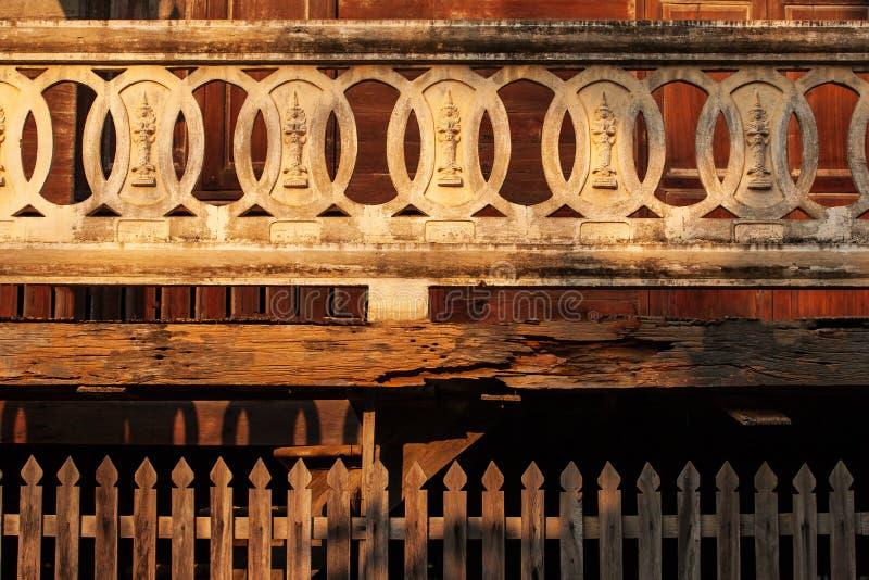 古老和美好的纹理、灰泥菩萨图象在灰泥圈子在阳台和木老织地不很细的柚木树 佛教寺庙在 免版税库存照片