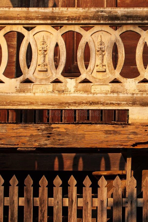 古老和美好的纹理、灰泥菩萨图象在灰泥圈子在阳台和木老织地不很细的柚木树 佛教寺庙在 免版税库存图片