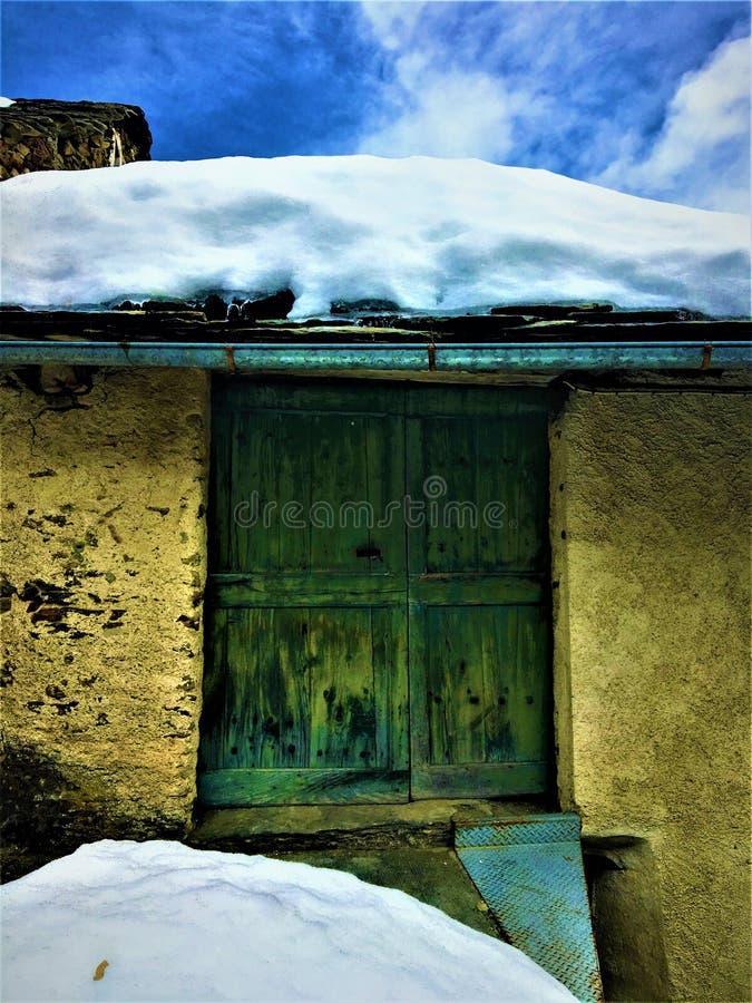 古老和葡萄酒绿色门、雪、魅力和历史 免版税库存图片
