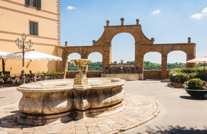 古老喷泉和曲拱在Repubblica广场,在皮蒂利亚诺, 图库摄影