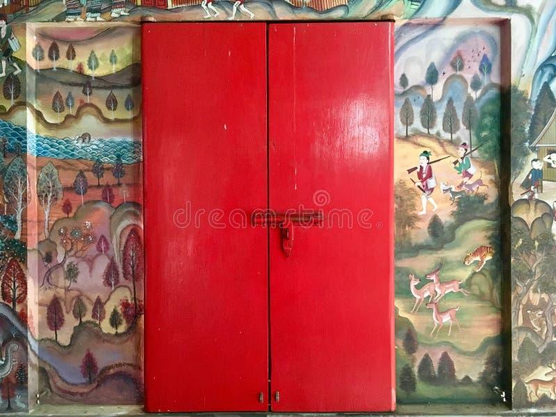 古老墙壁上的壁画和红色门在泰国寺庙 库存图片