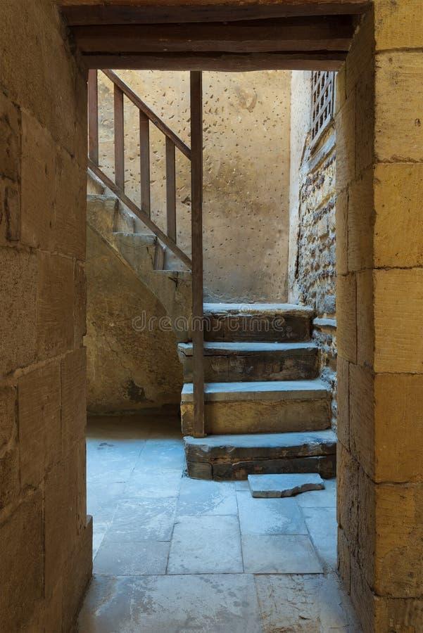 古老外在老砖显露与木楼梯栏杆的石墙和门道入口一个石楼梯 库存照片