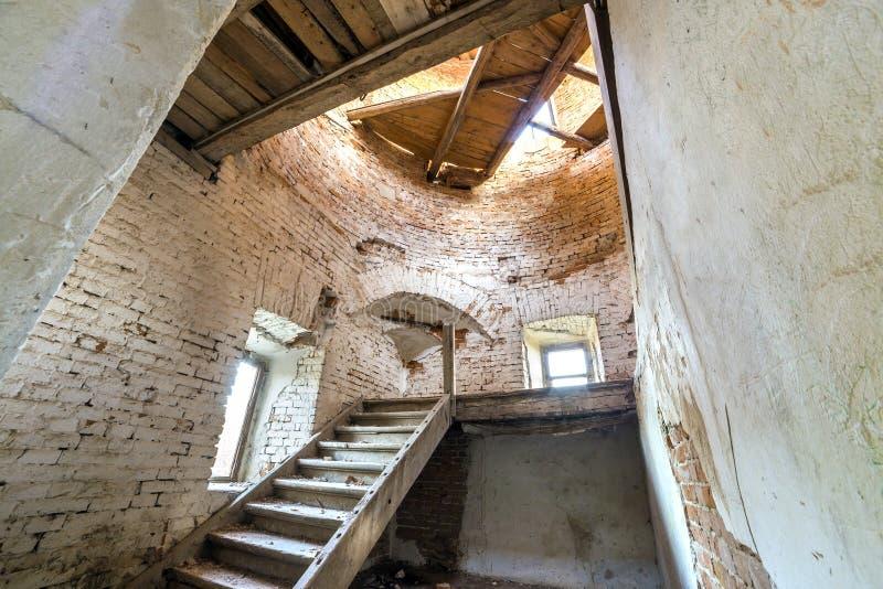 古老大厦大宽敞被抛弃的空的地下室有破裂的涂灰泥的砖墙的,小窗口室或宫殿,肮脏 免版税库存图片