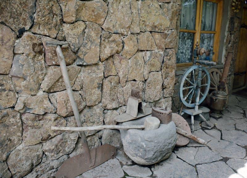 古老工具和每天对象在墙壁旁边 免版税图库摄影