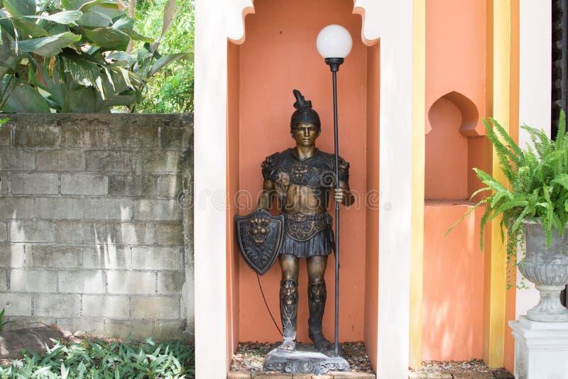 古老战士雕象由金属制成 金子和布朗 免版税库存照片