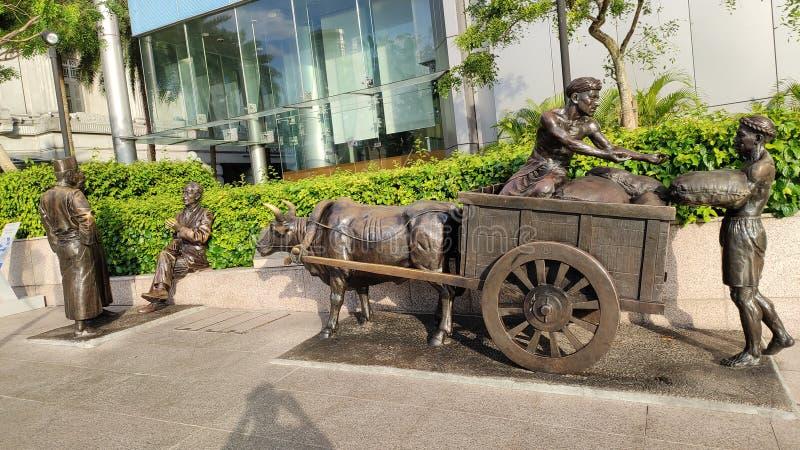 古老新加坡文化雕象使用牛车和人的谈论在路 免版税库存照片