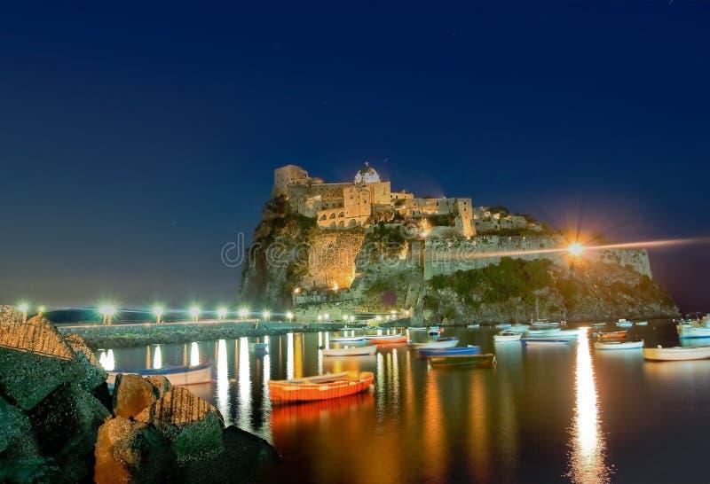 古老旅馆和城堡在坐骨海岛,意大利,在晚上 免版税库存图片