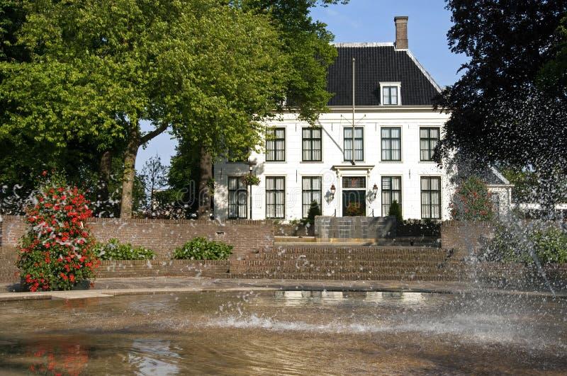 古老村庄大厅和喷泉在公园,希勒霍姆 免版税库存图片