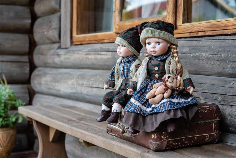 古老瓷玩偶坐手提箱在日志农舍附近 免版税库存图片