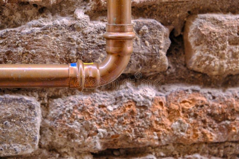 古老石墙和铜管子 免版税库存照片