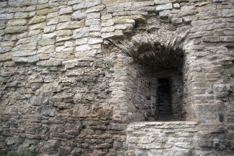 古老粉碎的石灰石堡垒墙壁的片段有发射孔的 免版税库存照片