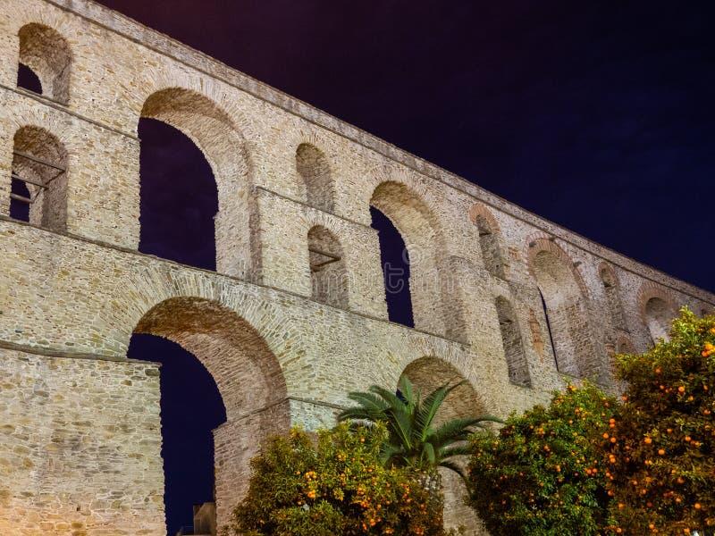 古老罗马渡槽、橙树和棕榈在它前面-夜射击-卡瓦拉,希腊 库存图片