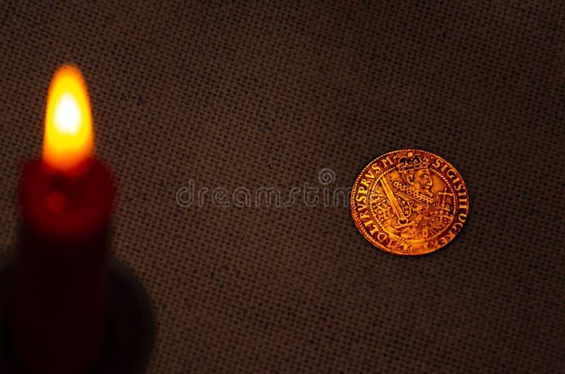 古老银币和燃烧的蜡烛 免版税图库摄影