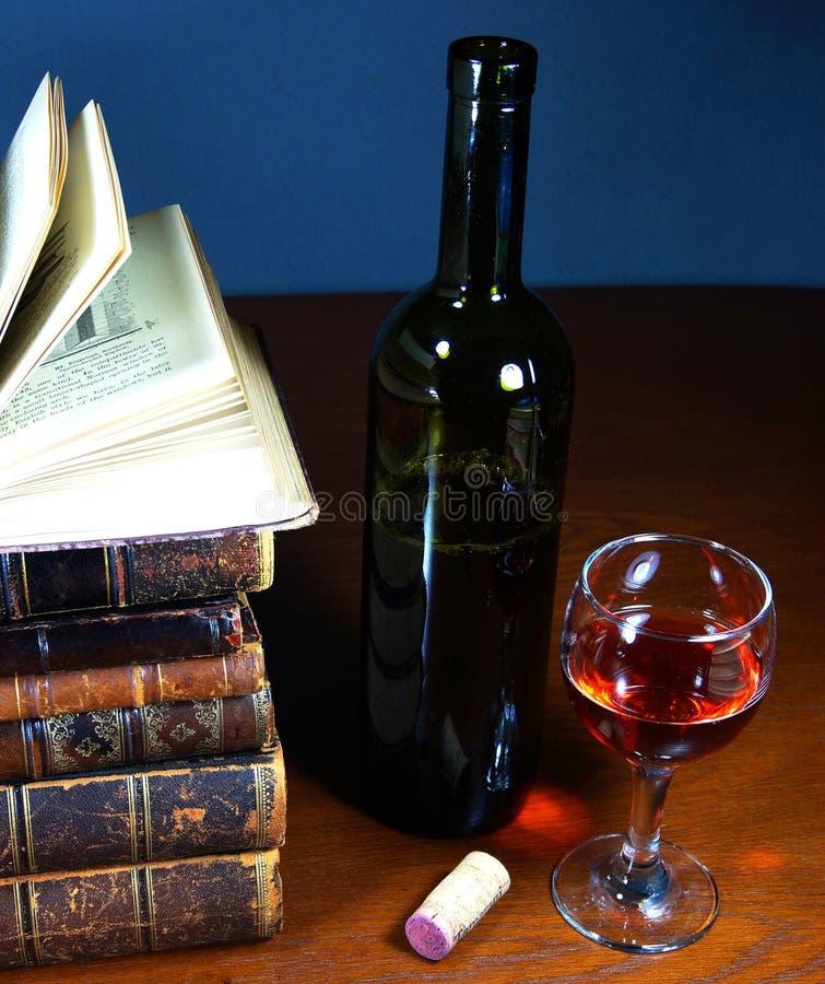 古色古香的书、一杯红葡萄酒和瓶 免版税库存图片