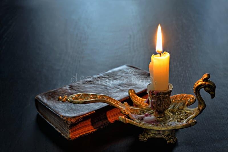 古色古香的书和射击的蜡烛在一张黑暗的桌上 库存图片