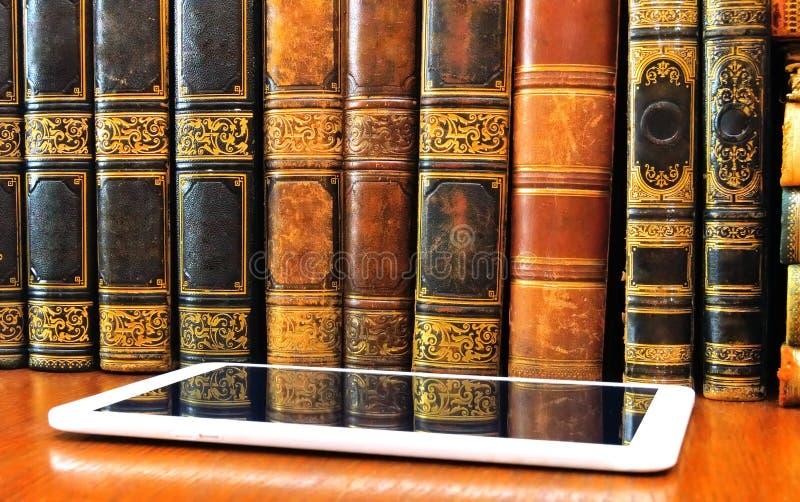 古色古香的书和片剂在桌上 免版税库存图片