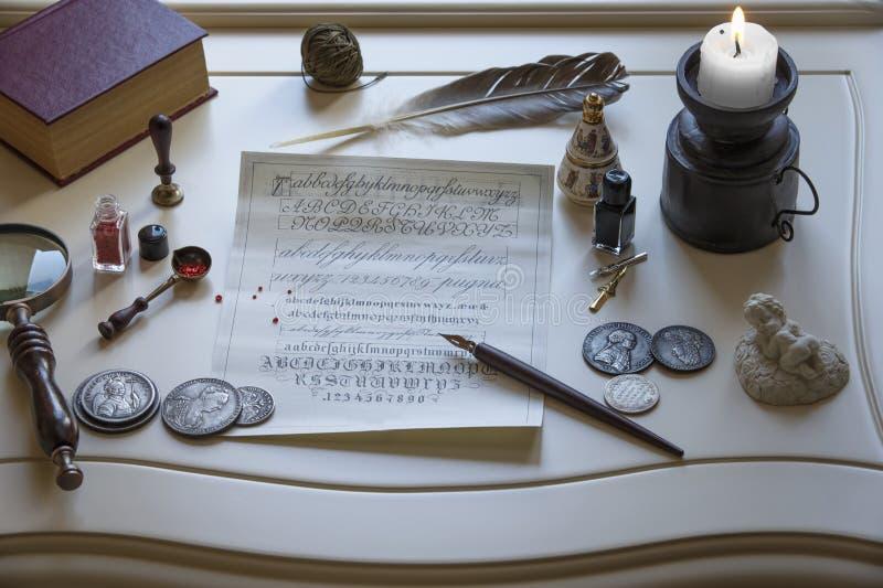 古色古香的书面材料和一个蜡烛在桌上 免版税库存图片