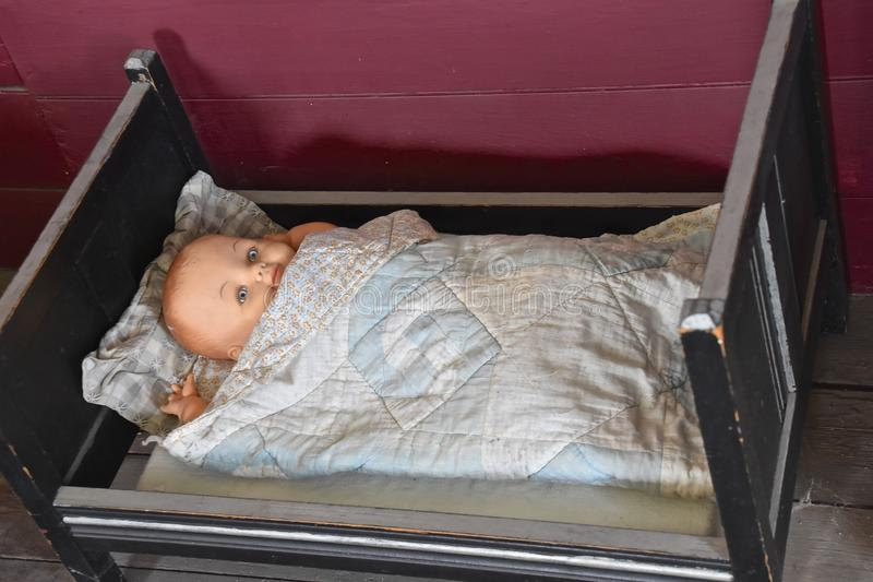 古色古香的儿童` s玩偶在一张微小的床上 免版税库存照片