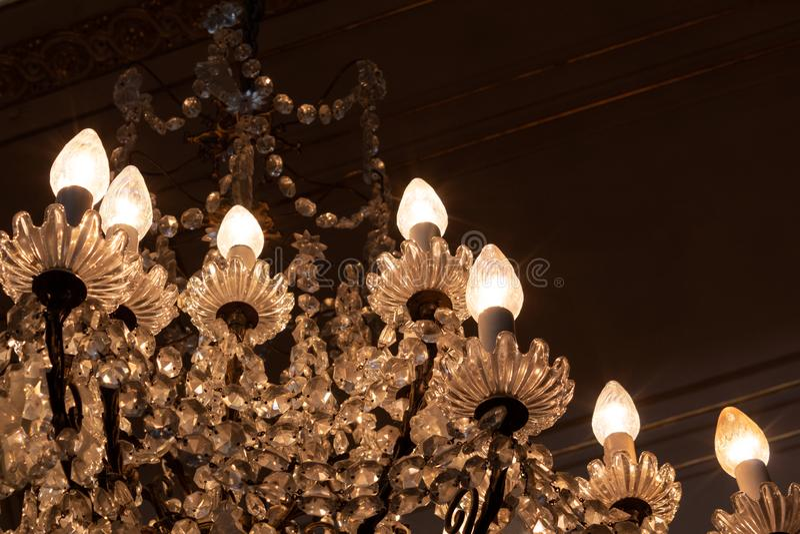 古色古香的华丽水晶枝形吊灯在一间变暗的屋子,拷贝空间 免版税库存图片