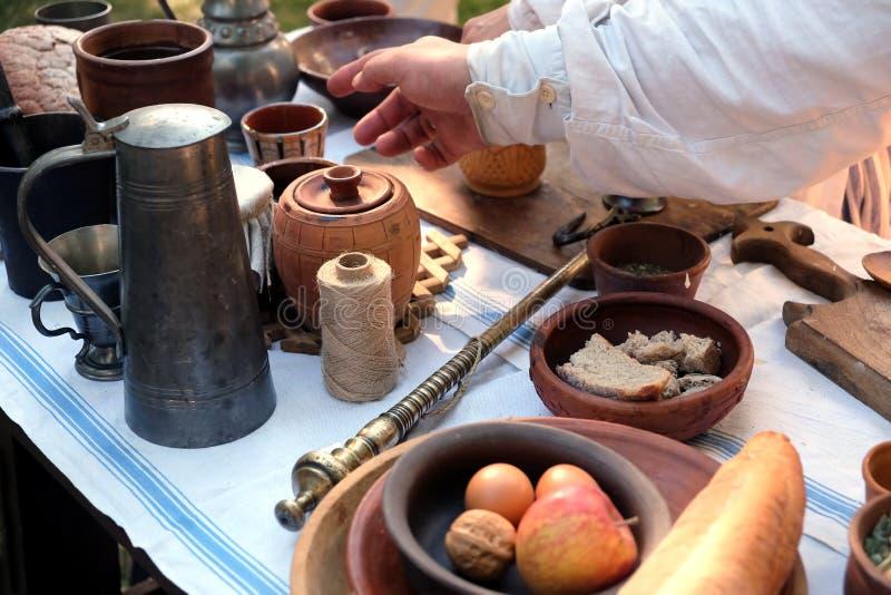 古色古香的器物、葡萄酒标度和简单的土气食物农村膳食在一张白色桌布户外,顶视图 免版税库存图片