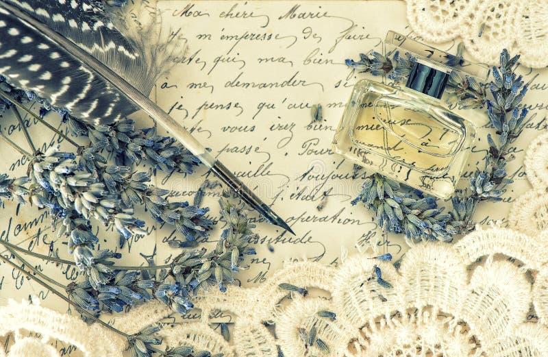 古色古香的墨水笔、香水、老情书和淡紫色花 免版税库存照片